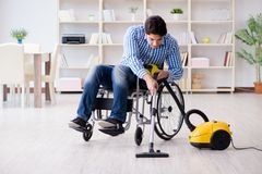 The disabled man cleaning home with vacuum cleaner Stock Image