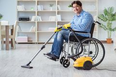 The disabled man cleaning home with vacuum cleaner Stock Images