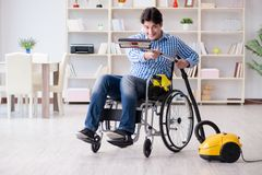 The disabled man cleaning home with vacuum cleaner Stock Photo