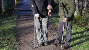 Disabled man on crutches with assistant at outdoor stock video