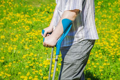 Disabled man with crutches on the dandelion field in summer Stock Photography