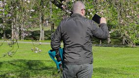 Disabled man with crutches filmed as blossoming apple tree stock video