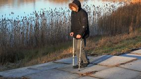 Disabled man on crutches near lake stock video footage