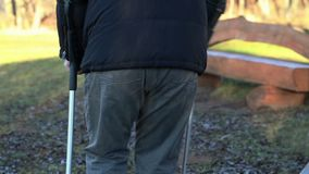 Disabled man on crutches at outdoor near benches stock footage