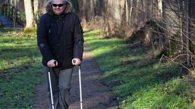 Disabled man on crutches at outdoor near benches in park stock video footage