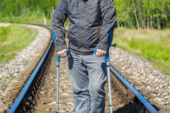 Disabled man with crutches on the railway Stock Photography