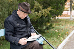 Disabled man on crutches reading in the park Royalty Free Stock Photography