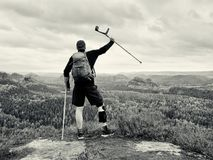 Disabled man on crutches on rock. Hurt knee in neoprene metal knee braces and man hold forearms crutches. Royalty Free Stock Photography