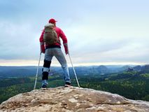 Disabled man with crutches stands on a big rock and looking to mountains at horizon. Stock Photo