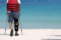 Disabled man with crutches while travel on the beach royalty free stock photos