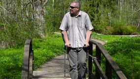 Disabled man with crutches walking on bridge stock video