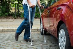 Disabled man with crutches walking near care Royalty Free Stock Image
