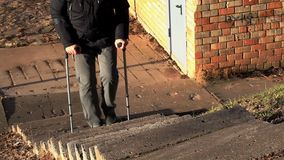 Disabled man on crutches walking up the stairs stock video