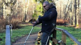 Disabled man with crutches on wooden bridge stock footage