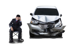 Disabled man and damaged car. Young businessman looks stressful, sitting on wheelchair next to a damaged car. Isolated on white background Royalty Free Stock Photos