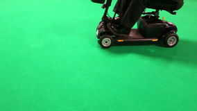 Disabled man driving mobility scooter. Handicapped man is driving electric mobility scooter on a green floor background stock video footage