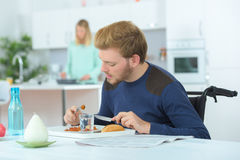 Disabled man eating with wife in background. Disabled men eating with wife in the background Royalty Free Stock Images