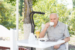 Disabled man enjoying coffee at a cafe Stock Images