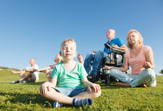Disabled Man with family practicing yoga outside. stock photos