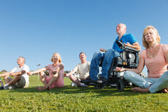 Disabled Man with family practicing yoga outside. Royalty Free Stock Images