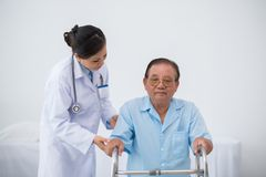 Disabled man. Female doctor supporting her patient with walker Royalty Free Stock Image