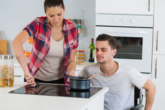 Disabled man and girlfriend cooking together Stock Photo