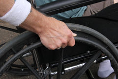 Disabled man with hand on wheelchair Stock Photos