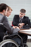 Disabled man and his co-worker talking with boss Stock Image