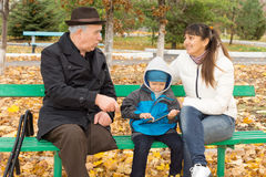 Disabled man with his daughter and grandson. Disabled elderly men with one leg amputated sitting on a wooden park bench outdoors playing with his daughter and Royalty Free Stock Photos