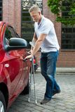 Disabled man holding crutches opening door of a car Stock Photos