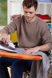 Disabled man ironing shirts at home Stock Photo