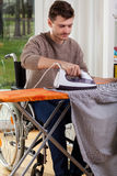Disabled man ironing Royalty Free Stock Images