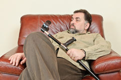 Disabled man in leather armchair Royalty Free Stock Photography
