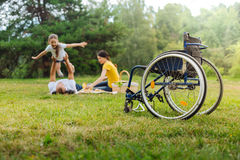 Disabled man lifting up his daughter on picnic. Play of imagination. The focus being on a wheelchair of a happy young men lifting up his little daughter Stock Image