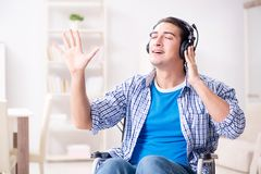 The disabled man listening to music in wheelchair. Disabled man listening to music in wheelchair Stock Photo