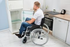 Disabled man look into a refrigerator Stock Images