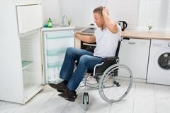 Disabled man looking in empty refrigerator Royalty Free Stock Photography