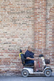 Disabled man on a mini car in front of a brick wall Stock Image