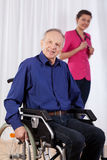 Disabled man and nurse in the background Stock Image