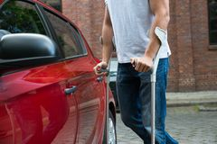 Disabled man opening door of a car Stock Photos