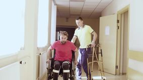 Disabled man in orthosis walking holding a walking frame