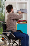 Disabled man placing shirt on shelf Royalty Free Stock Photography