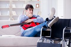 The disabled man playing guitar at home Stock Image