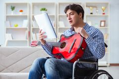 The disabled man playing guitar at home Stock Photo
