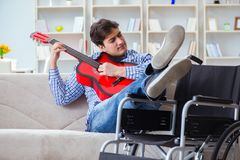 The disabled man playing guitar at home Stock Images