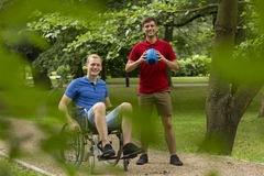Disabled man playing sport with friend. Disabled men on wheelchair playing sport in the park with his friend Royalty Free Stock Images