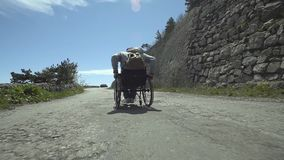 Disabled Man Pushes Himself Up The Road. Young traveler man sitting in wheelchair and pushes himself up the mountain road stock video