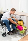 Disabled man putting towels into the washing machine Royalty Free Stock Photo