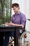 Disabled man reading a book at home Stock Photo