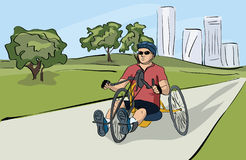 Disabled man riding bicycle at the park Stock Photos